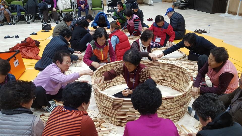 참가자들이 함께 나무토막을 쌓아올려 커다란 바구니 모양을 만드는 사진