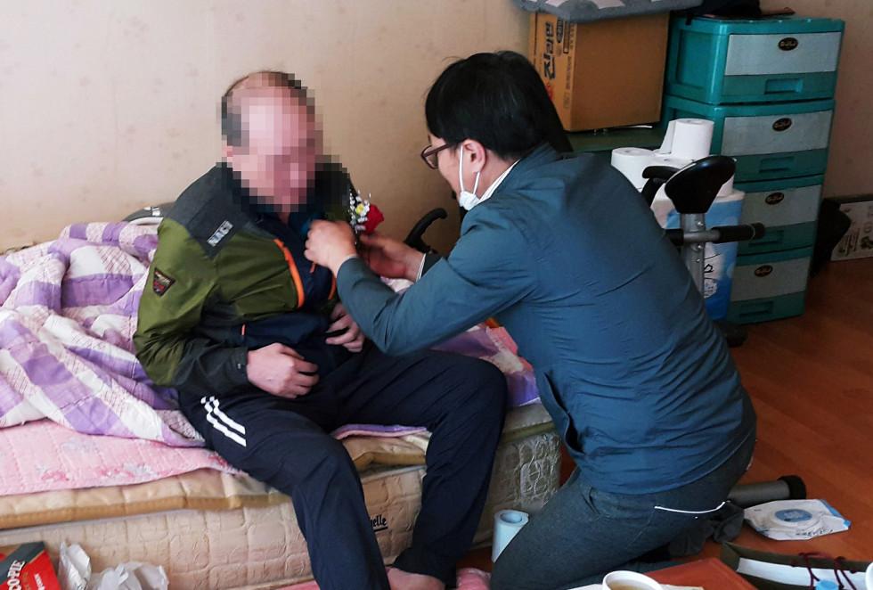 사회복지사 선생님이 재가독거 장애인 어르신에게   어버이날을 맞이하여 왼쪽 가슴에 꽃을 달아드리는 모습입니다