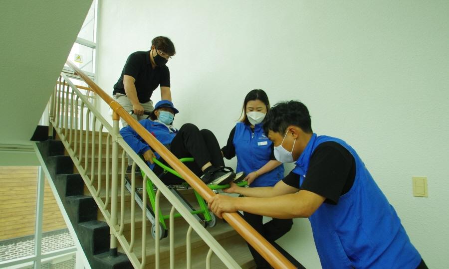 응급환자를 3명의 직원이 계단으로 이송 가능한 장비에 응급환자를 실어 계단을 내려오는 모습입니다.