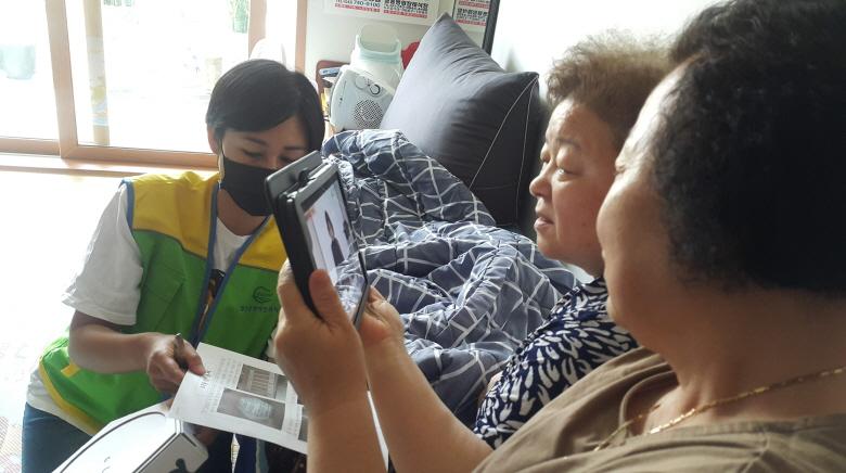 가정에서 테블릿으로 온라인 시청을 하는 장면입니다. 두 여성분이 같이보고 있고 옆에서 도움을 주시는 선생님이 계십니다.