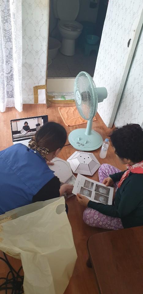 개인 집에서 한지공예를 연습하는데 복지관 직원이 도움을 주며, 영상강의를 따라하는 모습입니다.