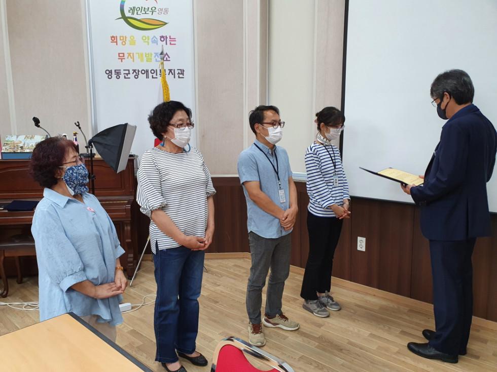수상자 4명이 서 있고 관장님이 전달할 상장을 들고 계시는 사진입니다.