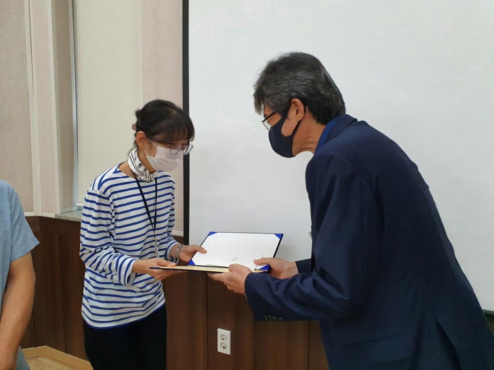 김지영 대리님이 관장님에게 상장을 받으며 악수하는 사진입니다.