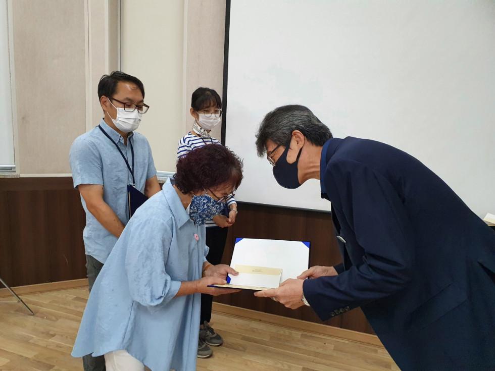 김옥순 선생님이 관장님에게 상장을 받으며 악수하는 사진입니다.