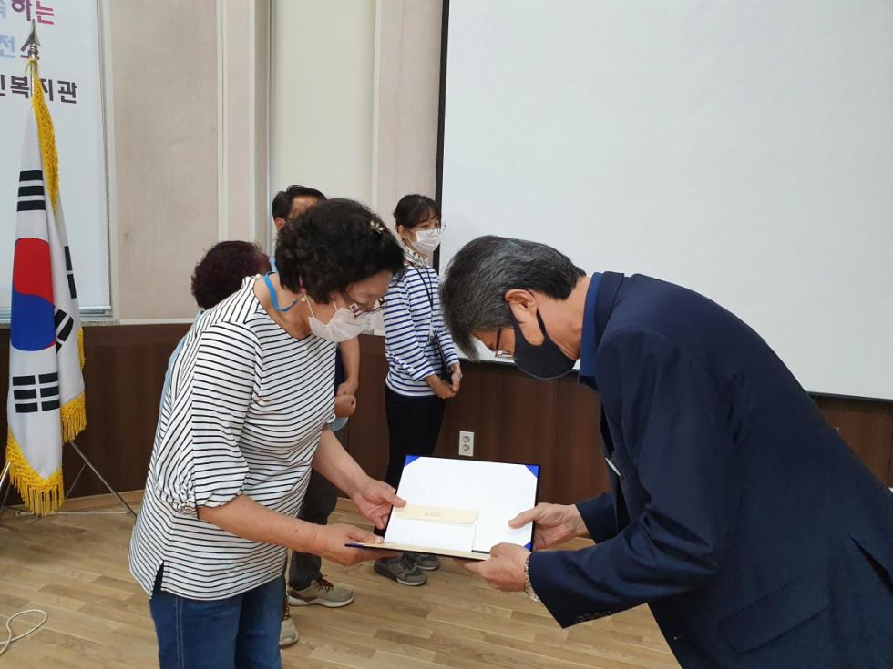 곽경자 선생님이 관장님에게 상장을 받으며 악수하는 사진입니다.