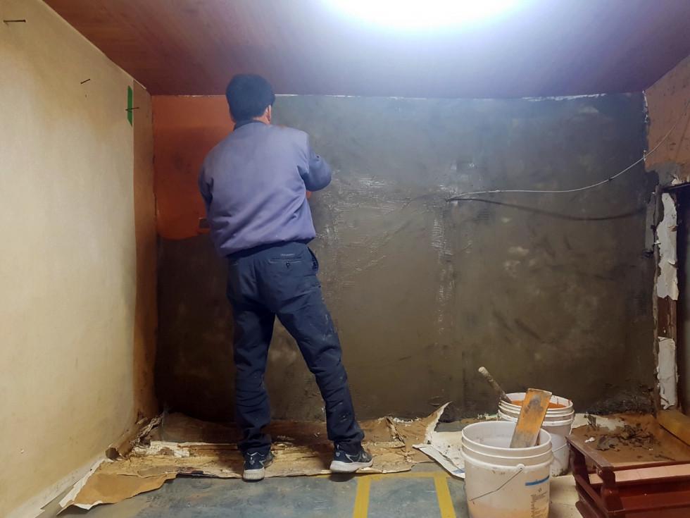방안 벽에 시멘트로 보수공사를 하는 모습입니다.