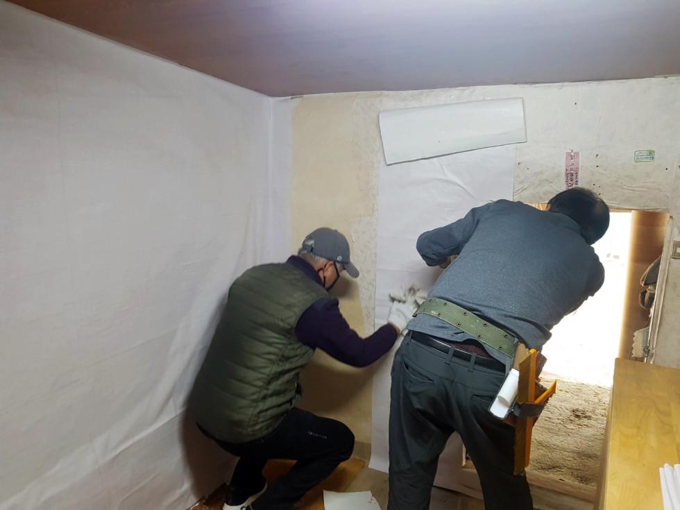 방안에서 두명이 벽지를 바르고 있는 모습입니다.
