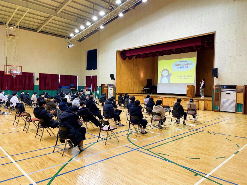 학생들이 강당 의자에 앉아 강의를 듣는 모습입니다. 강사는 강단에 올라가 스크린을 보며 강의중입니다. 사진 촬영 위치는 학생들 뒷편 오른쪽입니다.