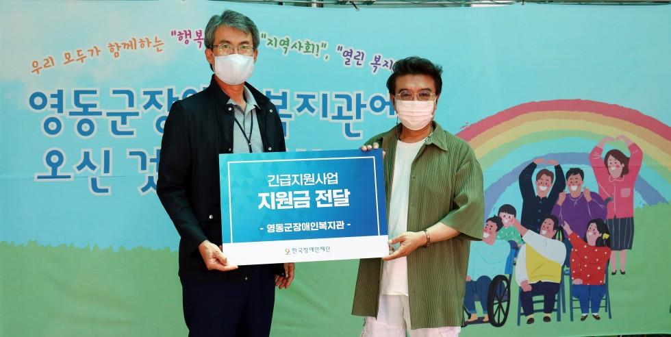 박병규 관장님과 한국장애인재단 이사장님이 긴급지원사업 지원금전달이라는 글자가 새겨져 있는 팻말을 두분이 같이 들고서 기념 촬영을 한 사진입니다.