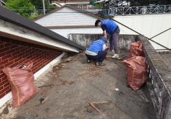 영동군장애인복지관 직원 2명이 지붕위에 올라가 기타여러 쓰레기를 치우는 장면입니다, 오른편에는 잡쓰레기가 가득찬 마대포대 2개 놓여 있습니다.